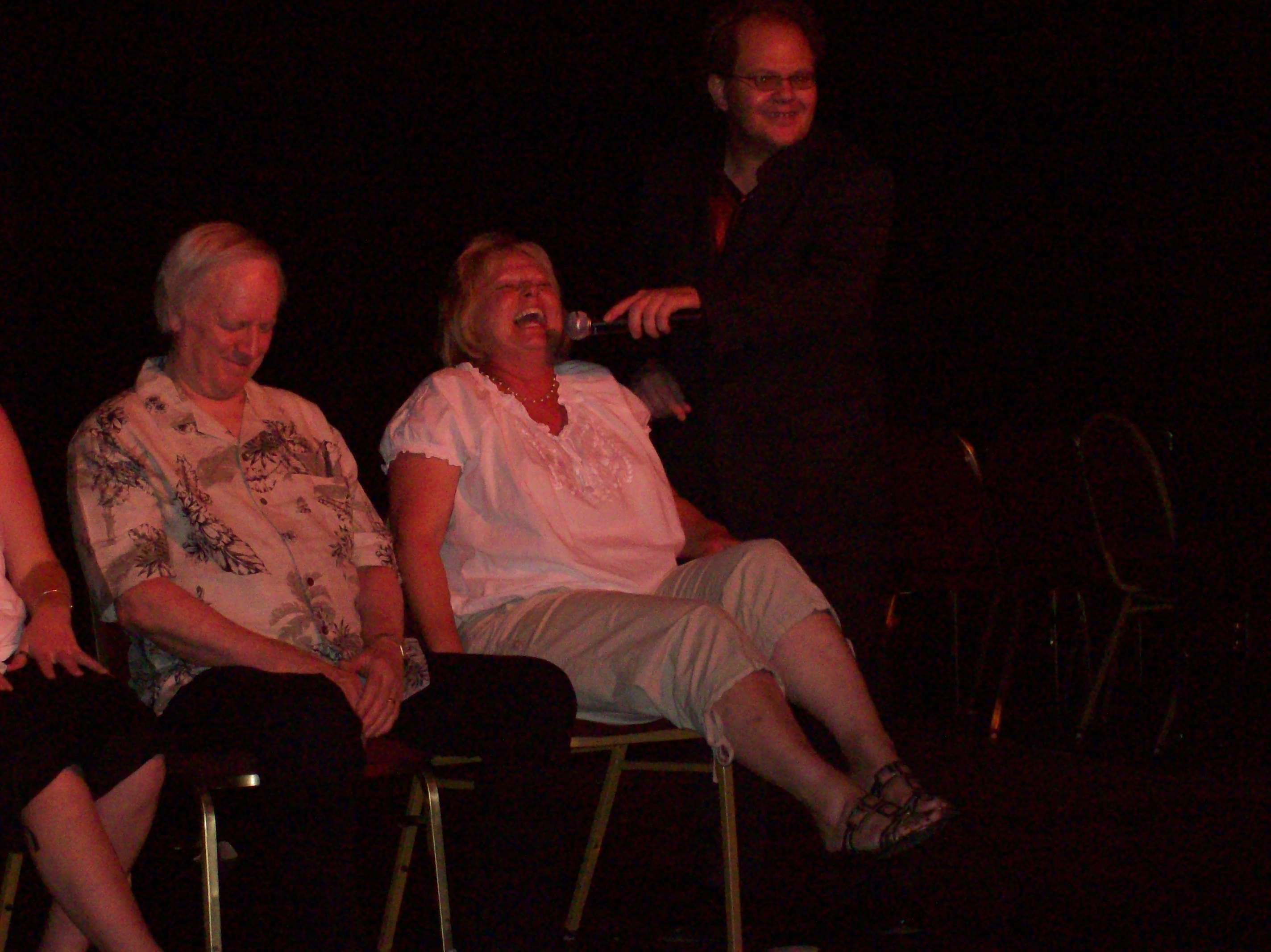 hypnotized woman laughs in comedy show Chis Cadys get hypnotized now playing in downtown reno nevada